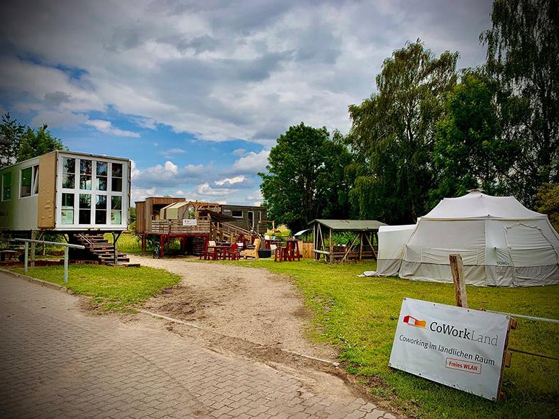 """Zelte, Container und Tiny Houses und eine Tafel mit der Aufschrift """"Coworkland – Coworking im ländlichen Raum. Freies WLAN"""""""