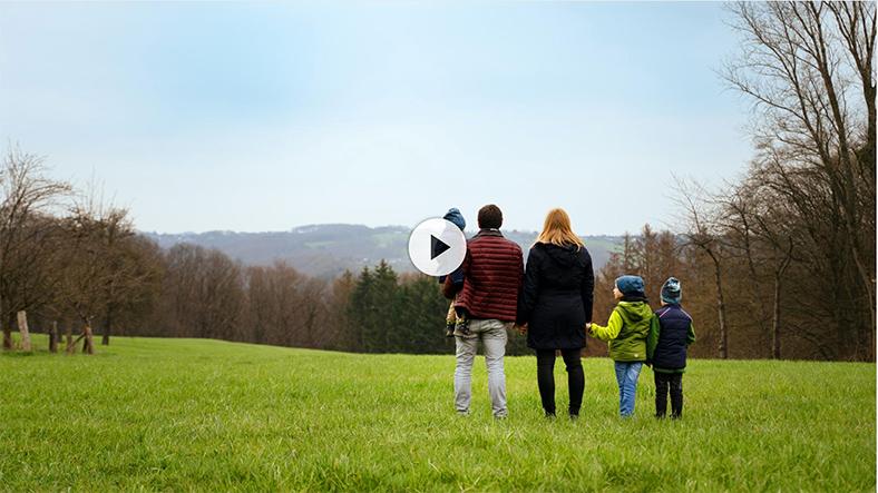 Szene aus dem Film: Familie mit drei Kindern geht über eine Wiese auf dem Land