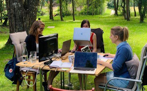 Drei Frauen arbeiten im Freien an Computern