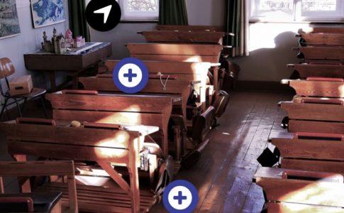 Ein historischer Dorfschul-Klassenraum mit Holzbänken. Es sind anklickbare Symbole zu sehen.