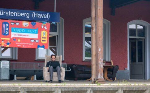 """Ein Mann sitzt in einem Sessel auf dem Bahnsteig, über ihm das Schild """"Fürstenberg (Havel)"""" und eine Werbetafel für die Veranstaltung """"jugend hackt"""""""