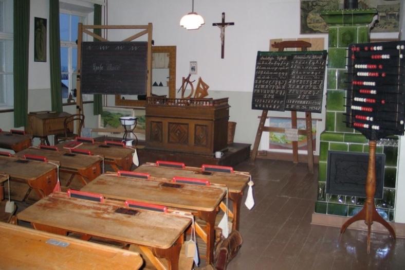 Ein historischer Dorfschul-Klassenraum mit Holzbänken, einem Rechenbrett und einem Kachelofen.