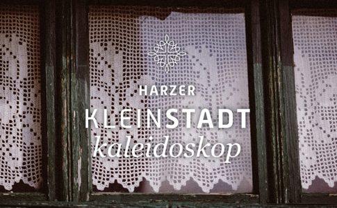 """Holzfenster mit Häkelgardine und Aufschrift """"Harzer Kleinstadtkaleidoskop"""""""
