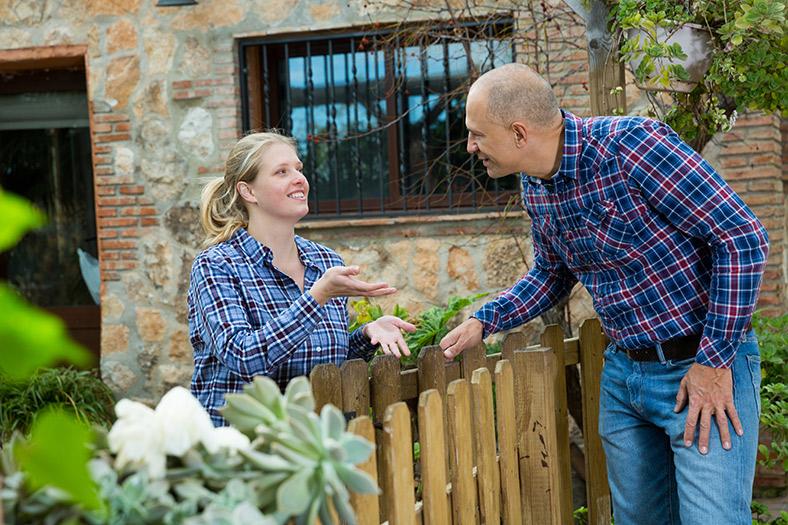 Zwei Personen unterhalten sich über einen Gartenzaun auf dem Dorf