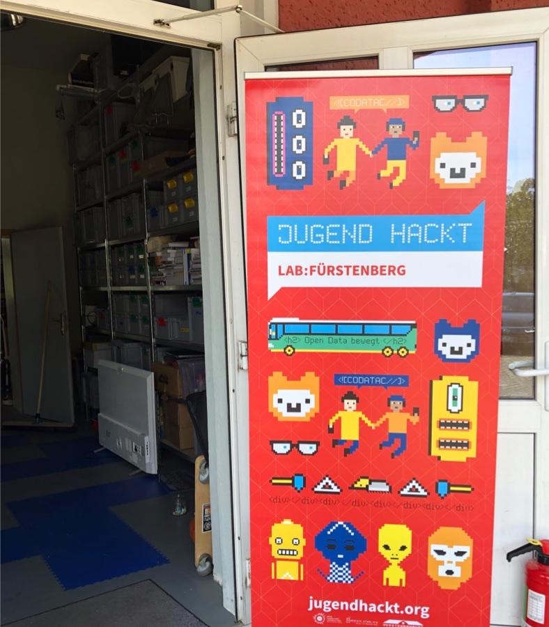 """Eine geöffnete Tür mit einer Werbetafel für den Jugendwettbewerb """"Jugend hackt"""""""