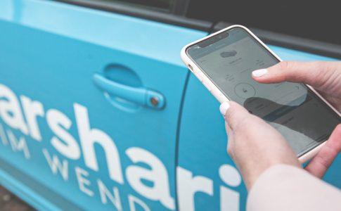 Eine Person öffnet mit Hilfe des Smartphones ein Carsharing-Fahrzeug