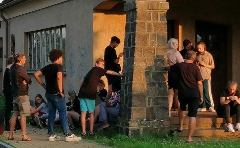 Eine Gruppe Jugendlicher vor einem historischen Gebäude nutzen Smartphones für eine Geschichtsrallye